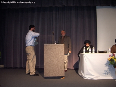 Sam Torabi, 1st from left, welcoming Imam al-Asi, 2nd from left, to the podium. Syed Abbas Ayleya is seated.