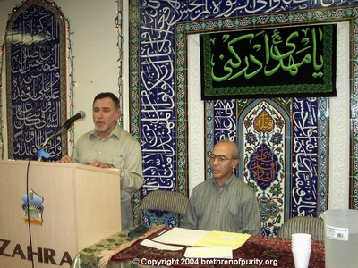 From left, Kays Hadi (a.k.a. Kays Hussein; a.k.a. Abu Haidar) lecturing on Asr-el-Zuhoor and, seated, Master of Ceremony Ali Pakfetrat.