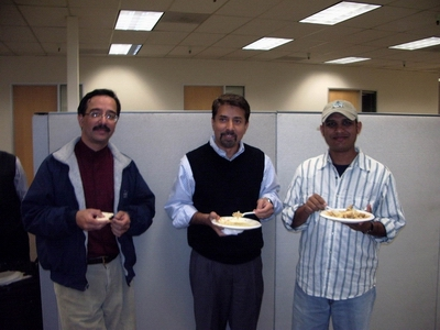Three members of Shia Association of Bay Area enjoying their Iftar meal while standing.